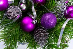 Christmas garland with silver glittercones and purple ornaments. Christmas garland with fir branch, silver glitter pine cones and purple ornaments on the white Royalty Free Stock Photo
