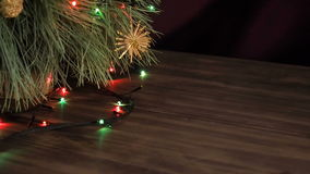 Christmas garland on the fir tree branches. Tree branches close up, shift motion, panorama. Flashing Christmas lights on Christmas tree with toys on wooden stock footage