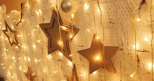 Christmas garland with Golden lights, close-up. Blinking Christmas stars Lights Twinkling. Winter Holidays Concept. stock footage