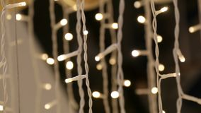 Christmas garland with Golden lights, in mall close-up. Blurred Christmas lights in shopping center. Bokeh. stock video