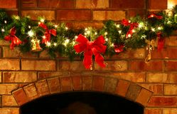 Christmas Garland with Lights. A Christmas garland on a brick fireplace, with fairy lights and red bows stock photo