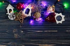 Christmas garland lights border ang golden toys on stylish black Stock Photos