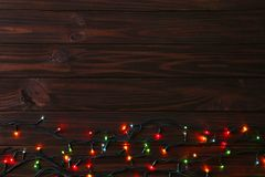 Christmas garland lights on brown background, copy space. Christmas composition royalty free stock photos