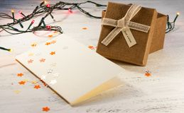 Christmas garland with lights and a gift box with a blank postcard on a light background. Christmas gift. Royalty Free Stock Photography