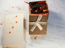 Christmas garland with lights and a gift box with a blank postcard on a light background. Christmas gift. Royalty Free Stock Image