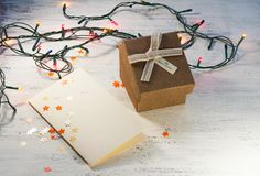 Christmas garland with lights and a gift box with a blank postcard on a light background. Christmas gift. Stock Image