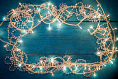 Christmas garland lights. Glowing Christmas garland and silver beads in a frame on a blue wooden background. Top view with copy space stock photo
