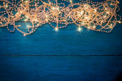 Christmas garland lights. Glowing Christmas garland and silver beads in a frame on a blue wooden background. Top view with copy space Stock Images
