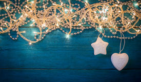 Christmas garland lights. Glowing Christmas garland and silver beads and toys on a blue wooden background. Top view with copy space Royalty Free Stock Photography
