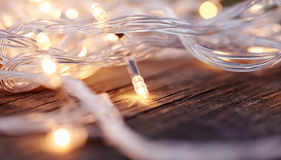 Christmas garland lights from LED bulbs. On the wooden background Royalty Free Stock Images