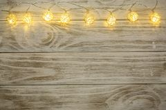 Christmas garland lights on old wooden background with copy space for your text. Top view Stock Photography