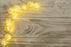 Christmas garland lights on old wooden background with copy space for your text. Top view Stock Images