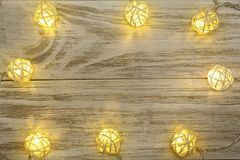 Christmas garland lights on old wooden background with copy space for your text. Top view Stock Photo