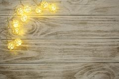 Christmas garland lights on old wooden background with copy space for your text. Top view Royalty Free Stock Image