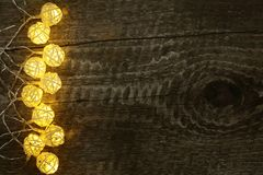 Christmas garland lights on old wooden background with copy space for your text. Top view Royalty Free Stock Photos