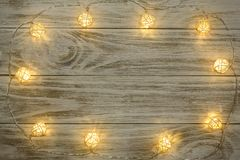 Christmas garland lights on wooden rustic background with copy space for your text. Top view.  Royalty Free Stock Photo