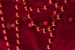 Christmas garland made from small red beads.On A Red Background Stock Images