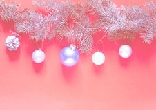 Christmas garland of from pine branches and silver balls on the background of coral. Color of the year 2019 concept. royalty free stock images