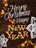 Christmas garland poster. With lettering Merry Christmas and happy new year in a retro style with decorations in garlands gloving and paper snowflakes on wood Royalty Free Stock Images