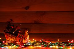 Christmas garland with a snowman in a sleigh with gifts. On wooden background.  stock images