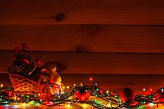Christmas garland with a snowman in a sleigh with gifts. On wooden background.  stock image