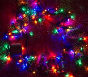 Christmas garlands of lamps on a red background with a pattern of gifts. Royalty Free Stock Images