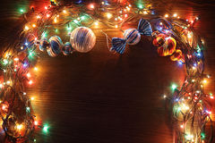 Christmas garlands of lamps on a wooden background. Stock Images