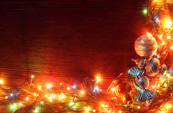 Christmas garlands of lamps on a wooden background. Royalty Free Stock Photos