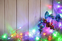 Christmas garlands of lamps on a wooden background. Stock Photo
