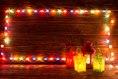 Christmas garlands of lamps on a wooden background. Royalty Free Stock Image
