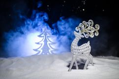 Christmas garlands in the tree form and figure of a deer on the street during a snowfall. stock images