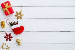 Christmas gif boxes, snow flake, red sock, christmas ball and candy cane on white wooden board. Royalty Free Stock Photography