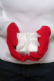 Christmas gift. Woman in white sweater and red gloves holding wrapped xmas present stock photography