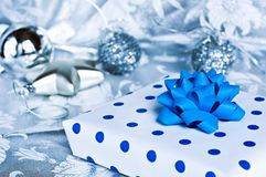 Christmas gift. Christmas polka-dot white and blue gift and silver balls in background Royalty Free Stock Photo