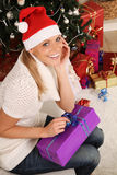 Christmas gift. Blond woman sitting on the floor with a christmas gift royalty free stock images