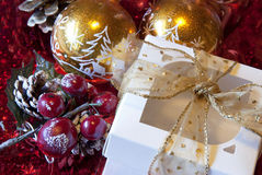 Christmas gift. A gift with gold ribbon and Christmas decorations on the table royalty free stock image