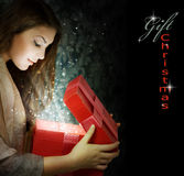 Christmas Gift. Beautiful Girl with Christmas Gift.With copy-space.Isolated on black Stock Photography