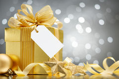 Christmas gift. With blank tag against bokeh lights background stock images