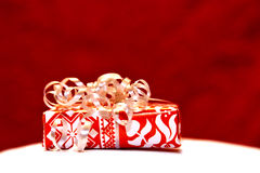 Christmas gift. Red wrapped christmas gift with red background stock photos
