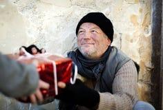 Christmas gift. For homeless man Stock Photos