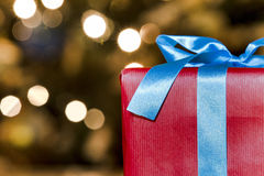 Christmas gift. With a blurred christmas tree in the background Royalty Free Stock Photo