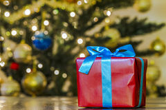 Christmas gift. With a blurred christmas tree in the background Royalty Free Stock Photography