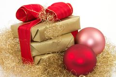 Christmas gift 3. Three golden gifts and two Christmas balls with a white background Royalty Free Stock Photos