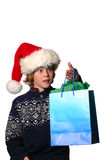Christmas Gift. Boy in santa hat surprised by gift Stock Images