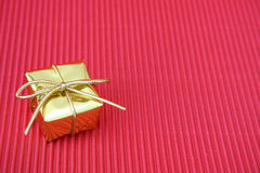 Christmas Gift. Small golden christmas gift on a red background Royalty Free Stock Image