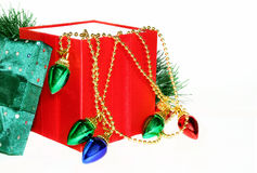 Christmas Gift. Red gift box with decorative garland of holiday lights and greenery on white background Stock Images