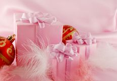 Christmas gift. Pink christmas gift with red ball on the pink background stock photos