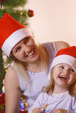 Christmas gift. Mother and daughte near christmas tree Royalty Free Stock Images