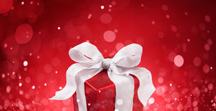 Christmas gift. Against red bokeh lights background royalty free stock image