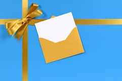 Christmas gift background, gold bow, blank greetings card with envelope Royalty Free Stock Photo